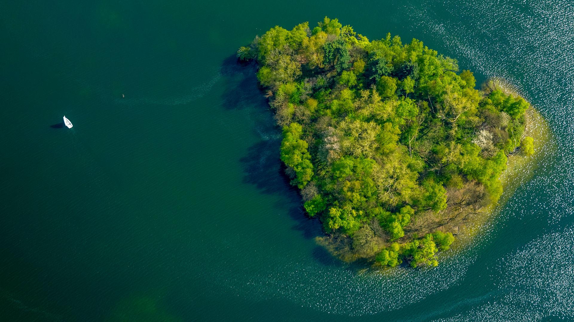 Boot auf grünem Unterbacher See mit Insel